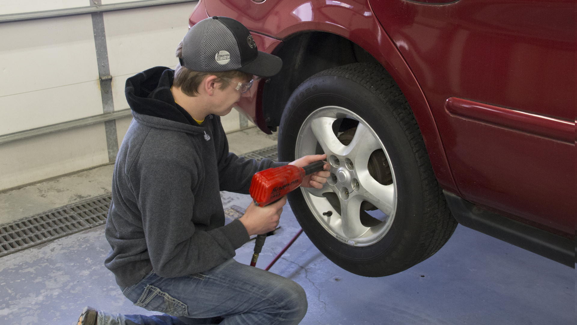 Male student changes car tire