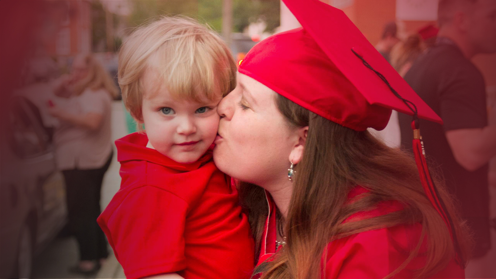 Graduate kisses young son