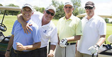 Four male golfers standing by each others and smiling at the camera.