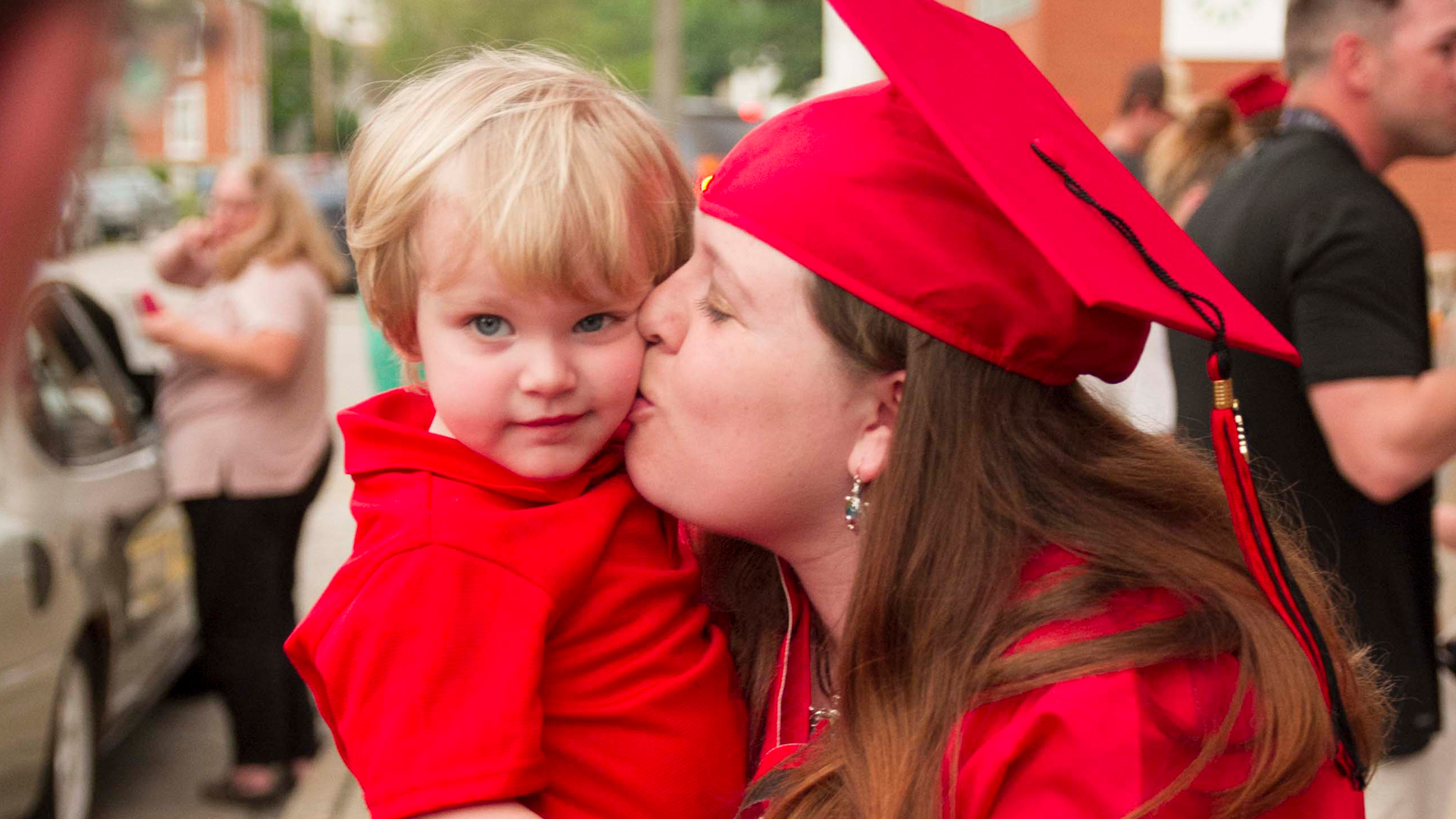 Graduating mother kisses young son